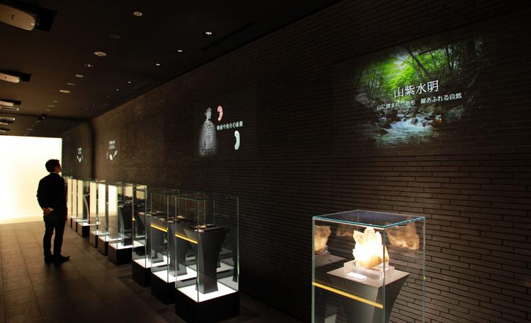 山梨県のジュエリーの歴史をたどる映像をレンガ調の壁面に映写。