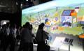 """『スマートコミュニティコーナー』 東レの材料技術が生かされた再生可能エネルギーによる将来の""""スマートコミュニティ""""を提案。<br> ワイド8mの大きな壁に描かれた街に重ねて写される映像と技術説明用の模型も一体となった複合演出です。"""