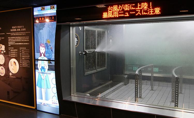 お天気キャスターが体験室の状況や暴風雨の危険を解説。<br>体験室内には、雨量と風速に応じた街の様子が実写で映し出されます。
