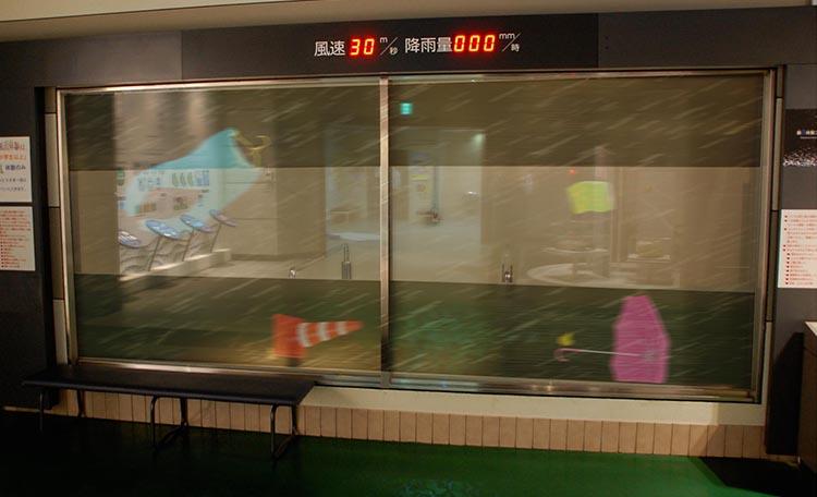 「暴風体験コーナー」  風速に応じた飛来物がガラス窓に投影される。