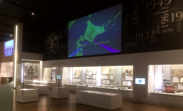 私たちの歴史 〜私たちの歴史のひろがりとつらなり<br>壁面グラフィックと一体になった大型スクリーン映像です。<br>マップ(場所)と年代(時間)を連動させながらアイヌ民族が辿ってきた足跡を紹介しています。